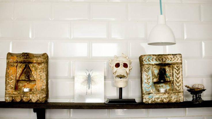 Kunst og kuriosa på 85 kvadrat - Aftenposten  KONTRAST: På en hylle på kjøkkenet står et indisk alter og en hodeskalle med miniatyrfrosker på hodet. Skallekunsten er laget av flodhestben. Lampen er fra Louis Poulsen. Den turkise tekstilledningen står i kontrast mot de hvite flisene og tar opp noe av fargen i alteret.