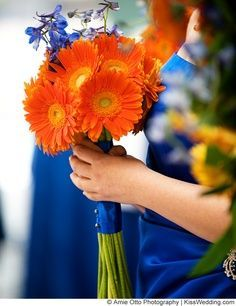 Use pale blue flowers and ribbon instead of royal blue. Orange gerber daisies.
