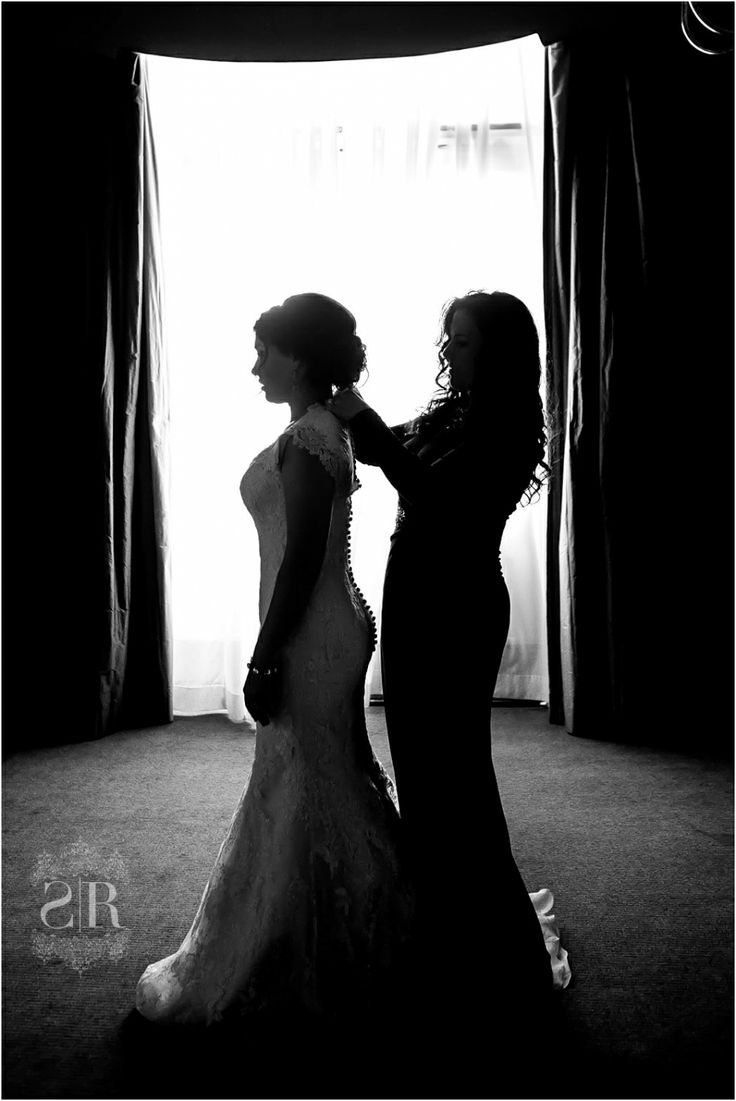 mother of the bride buttoning up the brides dress in silhouette mother and daughter moment on the day of the wedding