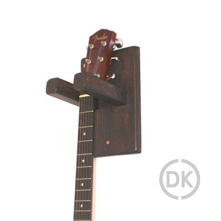 This is a hand crafted guitar wall hanger/mount, made of solid wood and is made to fit standard acoustic guitars. The shape and texture of the