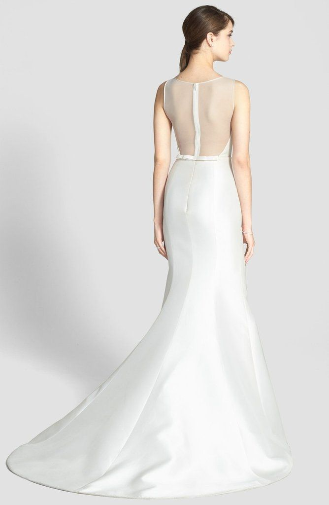 """Lustrous silk magnolia is paired with sheer illusion mesh to show stopping effect in this sophisticated wedding gown. The elaborately simple design highlights a lovely silhouette and flares to a dramatic trumpet hem with a short, elegant train. The upper back is beautifully sheer, save for the prominent back zip, and finishes with a sweet, narrow bow. 61 1/2"""" length. Bateau neckline. Sleeveless bodice. Fit-and-flare skirt. Fully lined. 57% silk, 43% polyester. Dry clean. By Amsale; ..."""