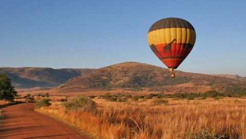 Hot air balloon moving over the landscape in the Pilanesberg National Park.