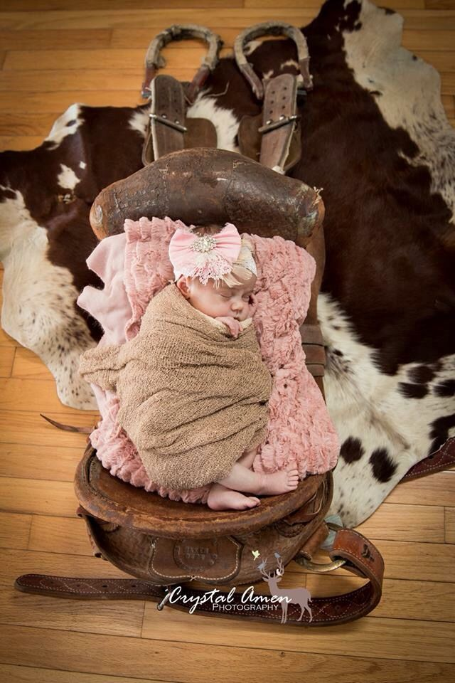 Newborn baby girl on daddy's bronc saddle -Crystal Amen Photography