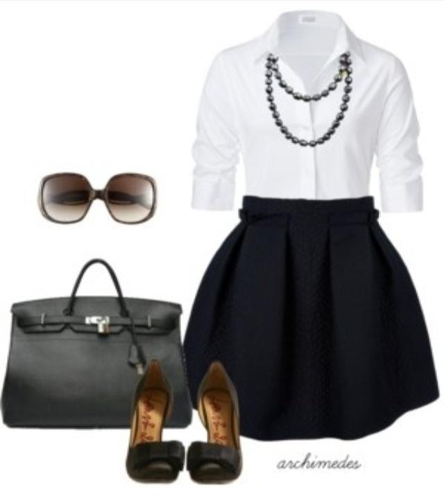 Gonna nera con fiocco, camicia bianca, scarpe nere aperte, borsa nera