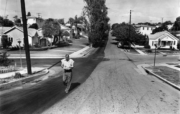 A tale of two cities. June 5, 1961: Constrasting street pavement on 64th Street marks border of cities of Los Angeles and Inglewood. Bob Cox of the Southern California Gas Co., walks just inside Inglewood side on left of photo.