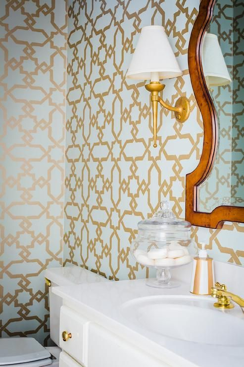 Blue and gold powder room features walls clad in blue and gold trellis wallpaper, Schumacher Cordoba Gold Wallpaper, lined with a…