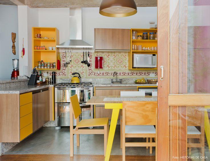 cozinha integrada com armários amarelos, piso de cimento e teto de concreto