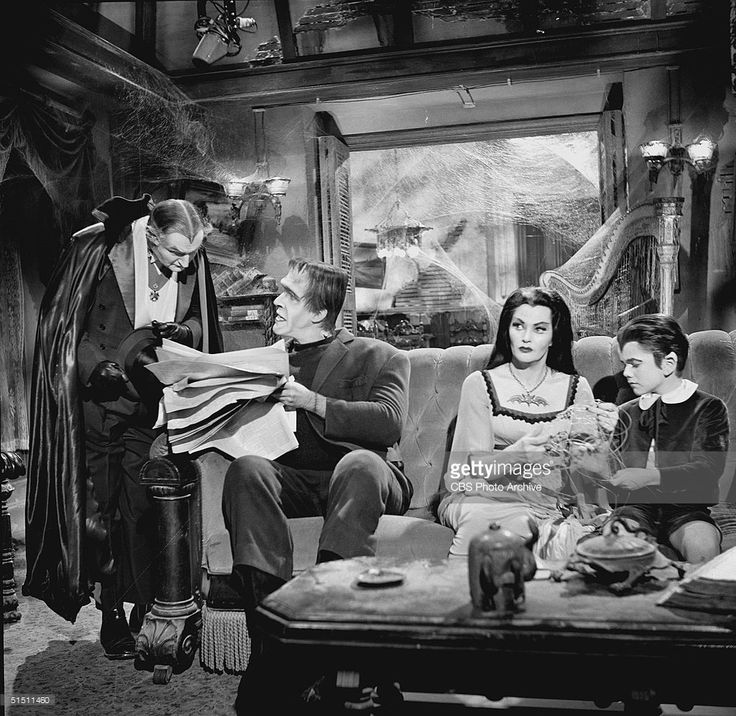 American actor and children's book author Fred Gwynne (1926 - 1993) (as Herman Munster) holds a newspaper and talks to Al Lewis (as Grandpa) while Canadian actor Yvonne de Carlo (as Lily Munster) and child actor Butch Patrick (as Eddie Munster) sit beside Herman on a couch and pretend to busy themselves while they secretly listen to the two men speak in a still from the CBS television situation comedy 'The Munsters' episode 'Grandpa Leaves Home,' November 11, 1964. The episode first aired…