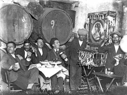 Αθήνα. Θαμώνες στο εσωτερικό ταβέρνας πίνουν με τη συνοδεία λατέρνας.