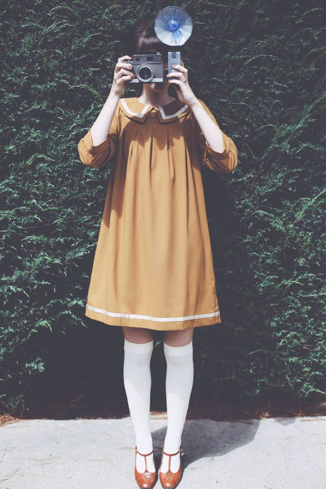 I love both the general feel of this photo, and her actual outfit. The color of the little vintage dress, the camera, the knee-high socks, not to mention the brown t-strap shoes (that look an awful lot like my wedding shoes I bought from modcloth)