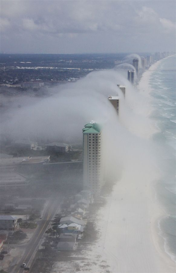 Tsunami in Florida? Nope. This is what's called a 'tsunami cloud,' rolling over some high-rise condos in the early morning hours. The 'tsunami cloud' effect is believed to happen when a fast-moving layer of fluid (like dew in a humid area) or air washes over a slower, thicker layer – creating a wispy wave effect like the one seen in this image.