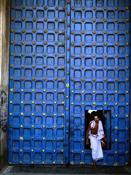 "Varadarajaswamy Temple, Kanchipuram ::   Photograph by Dinodia Dinodia, Photolibrary    ::    A man steps through a doorway at the Varadarajaswamy Temple in Kanchipuram, ""city of a thousand temples."" Kanchipuram is also known for silk saris—a thriving business here."