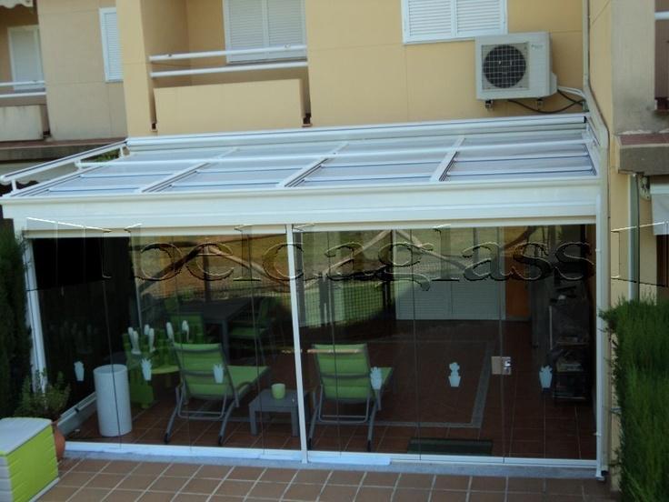 Cerramiento de terraza compuesto de techo movil deslizante y cortina de cristal, con toldo veranda por la parte superior.