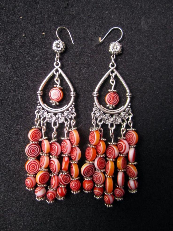 Spiral - 6      Långa örhängen med stora droppformade fästen och detaljer i silverpläterad metall. Hängande glaspärlor i Röd/Vit Spiralmönster samt nickelfria krokar.    Pris:  210 kr
