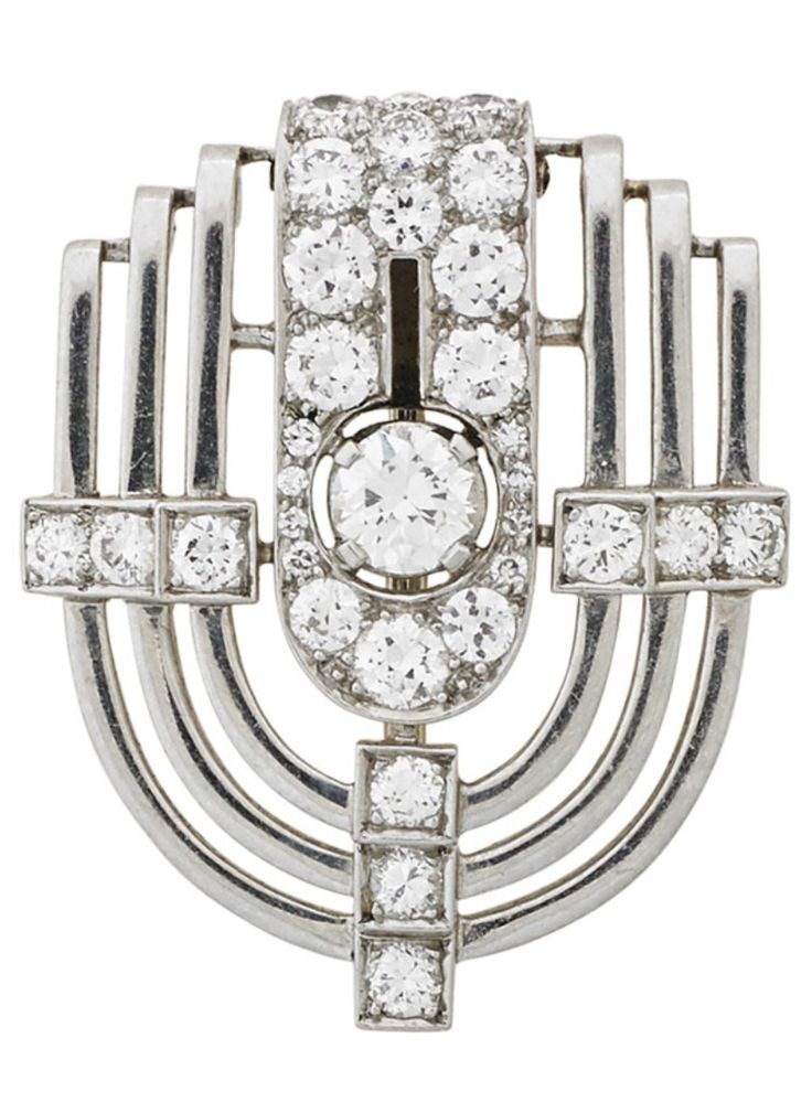"""CARTIER, INC. - AN ART DECO DIAMOND AND PLATINUM BROOCH, 1930-40. The stepped shield form with transitional cut diamond """"button"""" within a diamond pavé """"strap"""". Marked Cartier Inc., and numbered. 1 1/8"""" x 7/8"""". #Cartier #ArtDeco #brooch"""