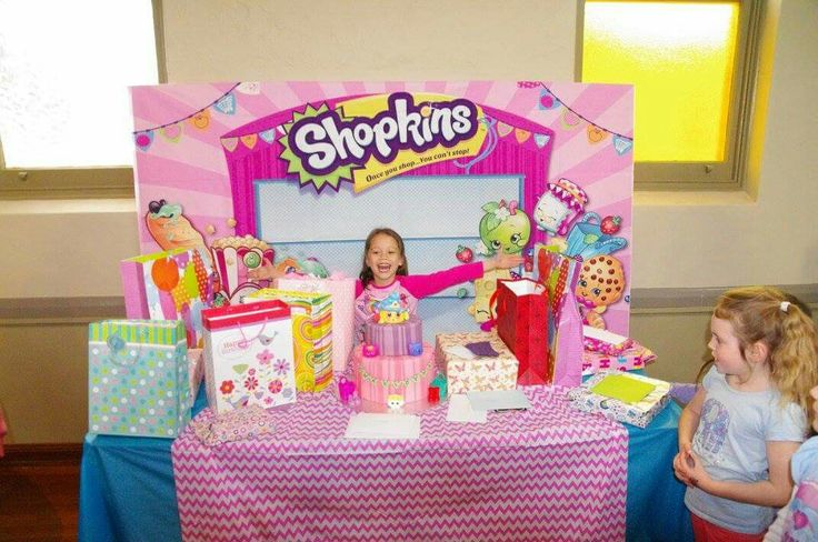 Shopkins backdrop ordered off eBay $20. Cake placed in centre of table and gifts were placed either side of cake