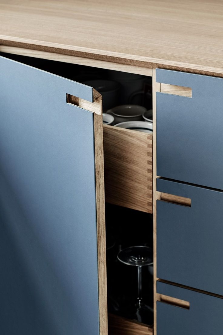 The surfaces are coated with a classic dark blue linoleum, whereas counter, drawers and details are made from solid oak.