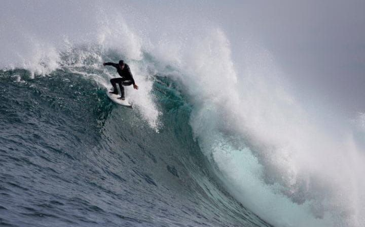 South African surfer Jake Kolnik rides a wave at Dungeons offshore reef in the Atlantic ocean outside Cape Town, South Africa. The big wave surfing season during the southern hemisphere winter is driven by storms in the South Atlantic which generate powerful swells that break on the Cape's outer reefs.
