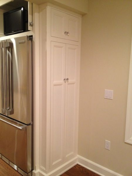 utility cabinetsat the edge of pantry to hold brooms