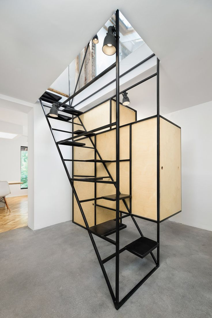 A sculptural staircase made from slender steel rods connects living spaces with an attic workplace