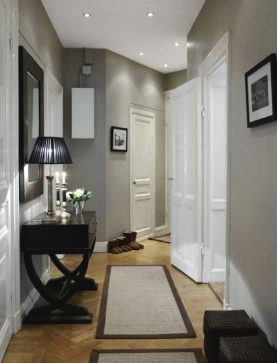 A transitional design hallway with elegant hall table, table lamp and mirror