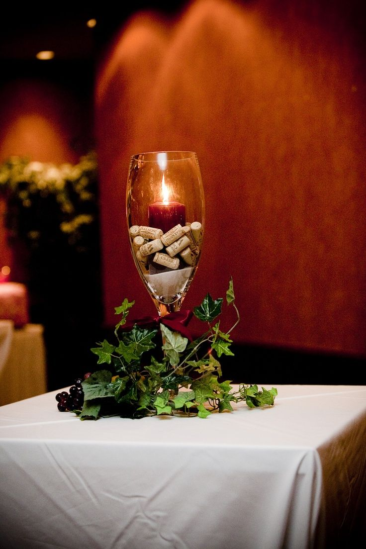 "So I have giant wine glasses for my center pieces and wanted to have the flower either inside on on top and fill the glass with corks like this...Wine-theme"" Wedding Centerpiece 