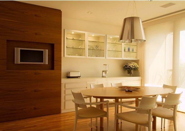 Sala de jantar com mesa oval de madeira + cadeiras brancas + pendente cromado + louceiro branco + painel de madeira. Projeto A1 Arquitetura, via Decorando com Classe.