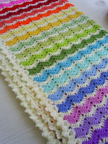 crochet blanket: 20  different colors separated by cream with a flower edging