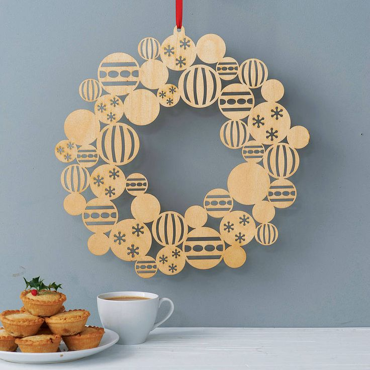lasercut wreath made up of clusters of patterned christmas baubles. natural wood finish