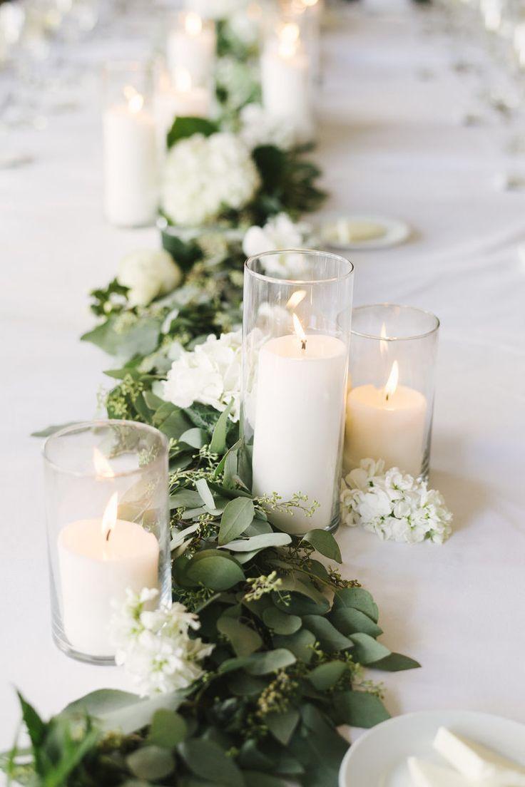 Décoration de table avec feuillage et bougies blanches dans des photophores
