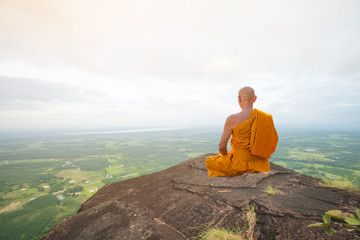 buddhist monk in meditation at beautiful nature on high