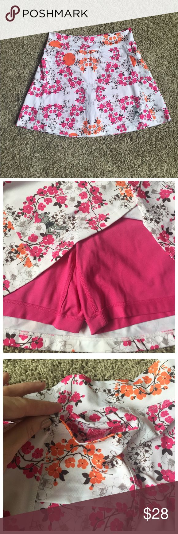 """Running Skirts Cherry Blossom Print Athletic Skirt Bright pink, orange, and chocolate print on white background.  Underneath are bright pink compression shorts.  There are 2 roomy pockets at the hip with Velcro closure (see photo).  Length approx. 15"""".  Skirt is listed as Size 2, which according to sizing chart for Running Skirts is a waist measurement of 27-28"""" and women's pants size 4-6.  Worn a few times, excellent used condition. Running Skirts Shorts Skorts"""