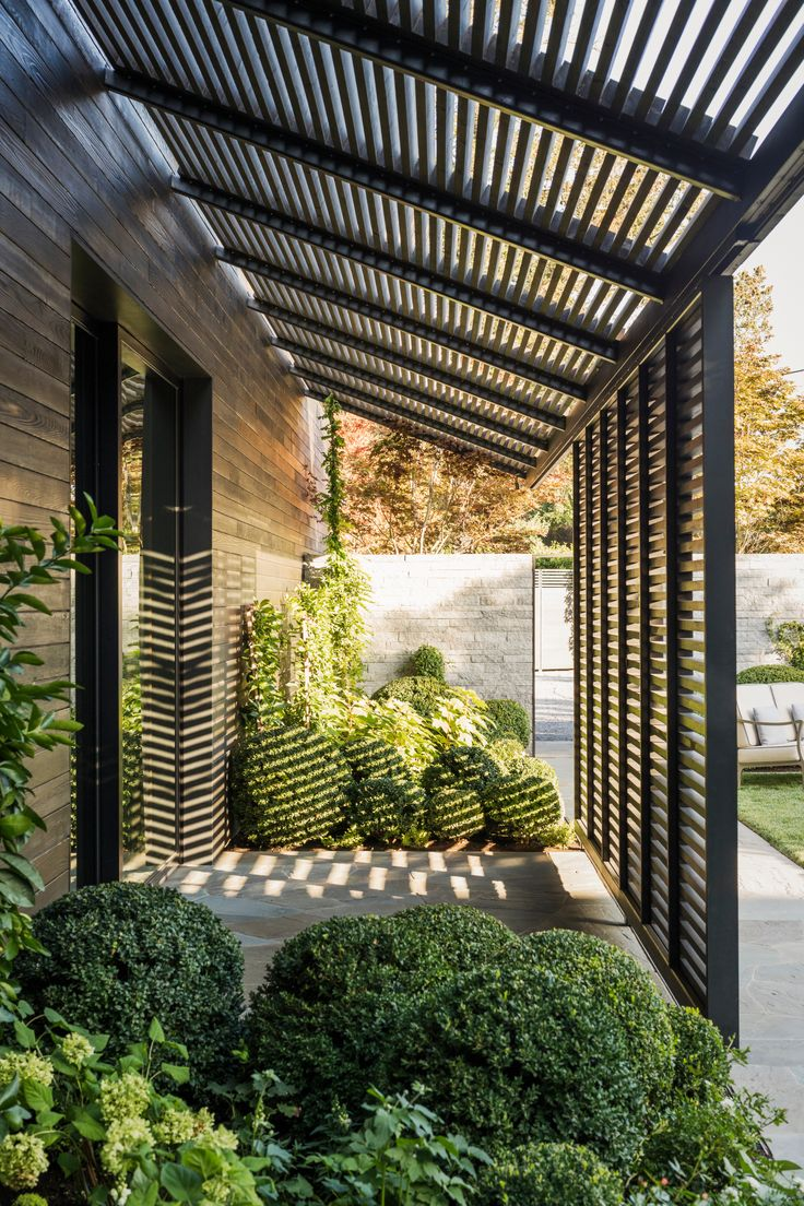 Flush at the corners where the eaves of the roof meet the siding, the kitchen's streamlined body is partly clad in charred wood. #frenchlaundry #sideyard