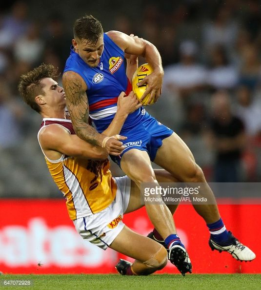 Clay Smith of the Bulldogs is tackled by Ben Keays of the Lions during the AFL 2017 JLT Community Series match between the Western Bulldogs and the...
