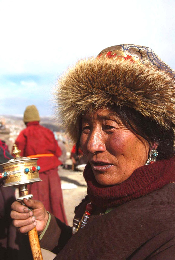 A woman pilgrim spinning her prayer wheel  |China photo