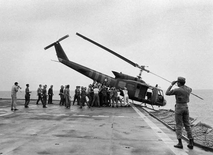 U.S. Navy personnel aboard the USS Blue Ridge push a helicopter into the sea off the coast of Vietnam in order to make room for more evacuation flights from Saigon. The helicopter had carried Vietnamese fleeing Saigon as North Vietnamese forces closed in on the capital.