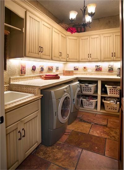This laundry room provides space for laundry baskets, a counter over the duet washer/dryer, and finishes off the laundry sink.  Addition storage cabinets are a welcome addition. Traditional (Victorian, Colonial) Laundry Room by Mari Woods