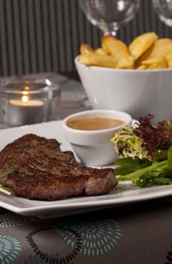 Medium - Rare Sirloin Steak with a side of Chunky Chips and Creamy Pepper Sauce on top of Royal Porcelain Titan Crockery