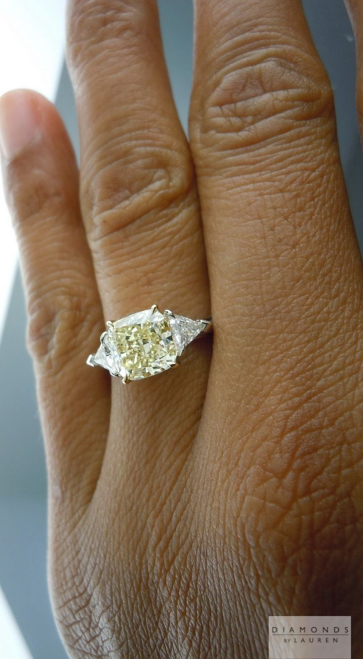 yellow cushion cut diamond ring. Obviously not this huge but, I love the triangle diamonds on the side, it adds a nice touch