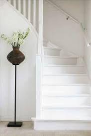 trappa med rund handledare och väggen på andra sidan som möter spjälorna