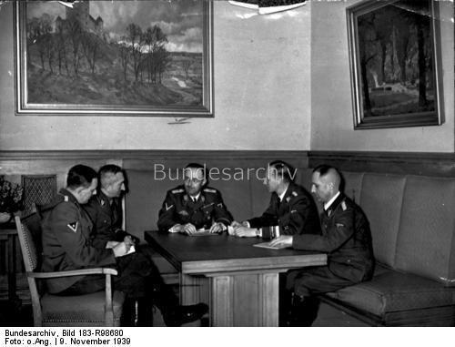 Der Reichsführer SS Heinrich Himmler bespricht mit dem Chef der Sicherheitspolizei Reinhard Heydrich und dessen Mitarbeitern des bisherige Ermittlungsergebnis über den Bombenanschlag im Bürgerbräukeller in München am 8.11.1939 und legt die Grundlinien für die weitere Bearbeitung fest. UBz: v.l.n.r.: SS-Obersturmbannführer Huber, SS-Oberführer Nebe, Reichsführer-SS Heinrich Himmler, SS-Gruppenführer Reinhard Heydrich und SS-Oberführer Müller - 27.11.1939