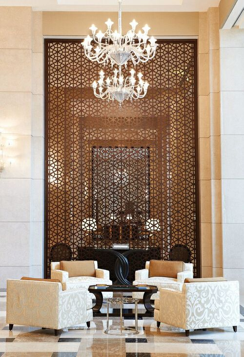 Metal laser cut panel with moroccan pattern, marble tiled floor, venetian glass chandelier #hotel #decor