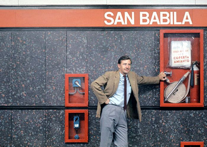 Bob Noorda in front of signage, designed by him, of Milan Metro