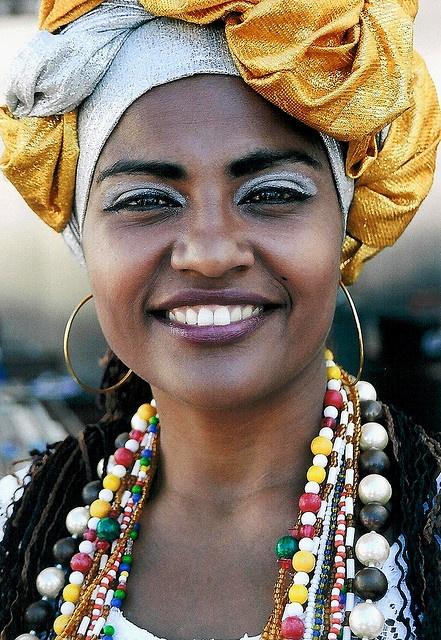 **** Le BRÉSIL EST DANS SON CARNAVAL. LE MODÈLE DES BAHIANAISES : la femme NOIRE MATURE aux AMPLES ATOURS BLANCS, avec le COLLIER a RANGS MULTIPLES (BALNGANDAS) au cou... Baiana. Bahia, Brasil. Remarquez les BOUCLES d'OREILLES... Bahia Brazil.