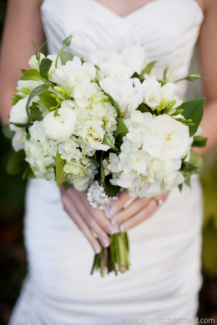 Designed by Fresh Weddings by CarryAnn http://freshweddingsbycarryann.com  white hydrangea, white lisianthus, white renenculas, white freesia, and greens.  Photo by Jen and Chris Creed Photography.