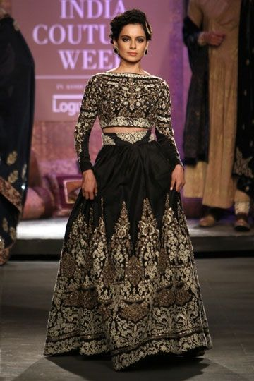 Kangana Ranaut in Anju Modi Although there is a lot of embroidery on this piece, it doesn't give a heavy vibe. Kangana Ranaut breezed down India Couture Week 2014 in this gorgeous black Anju Modi lehenga that is every bit chic as it is traditional. The long sleeve blouse, up do hair, dark-eyes-nude-lips makeup with button statement earrings and hair accessories all add to the modern / contemporary elements to look. Perfect for a Reception event! Indian couture #thecrimsonbride