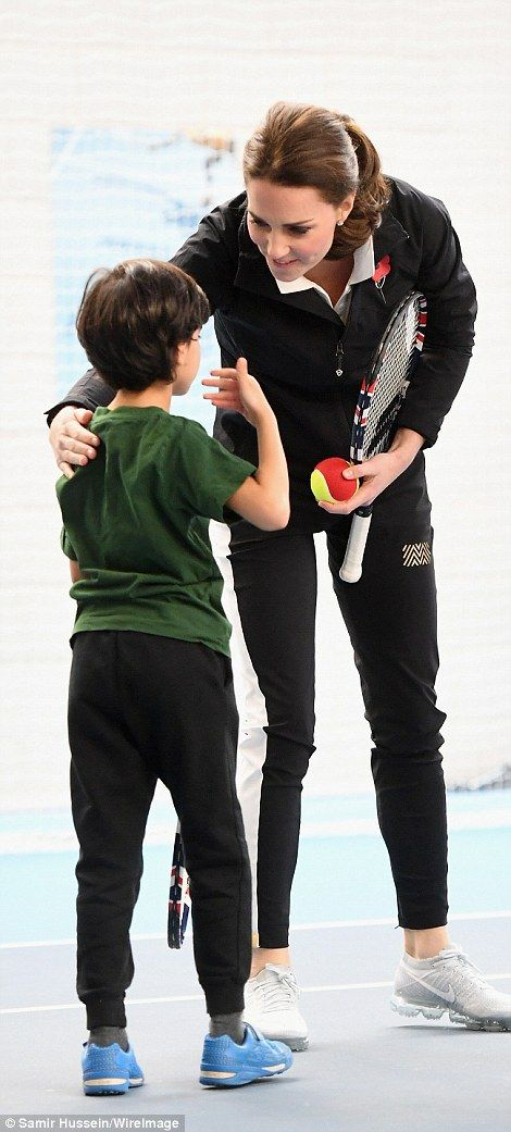 The Duchess put a reassuring hand on the shoulder of a young boy as they chatted about tennis during the visit