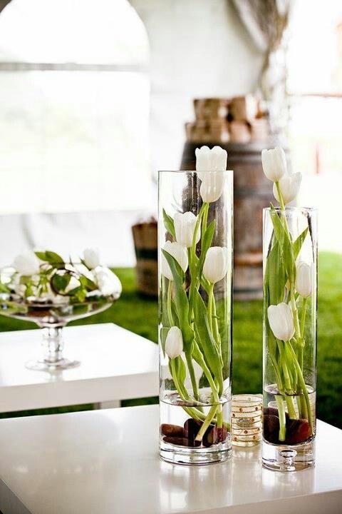 Des fleurs dans un grand vase cylindrique.
