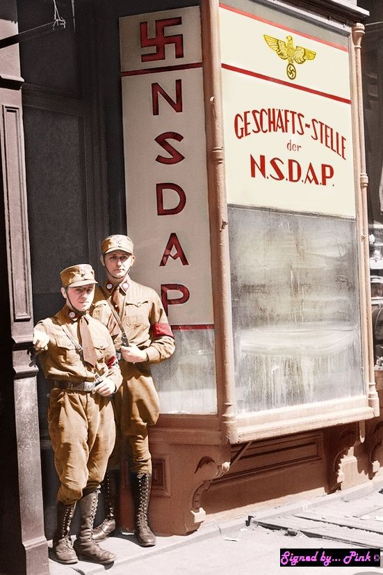 Two American members of the National Socialist German Workers Party dressed in full uniform, stand near a stand containing promotional content for the Party while they encourage their fellow Americans to read some of the material, especially since most Americans had little to know knowledge about the NSDAP or what it stands for. New York City, 1934.