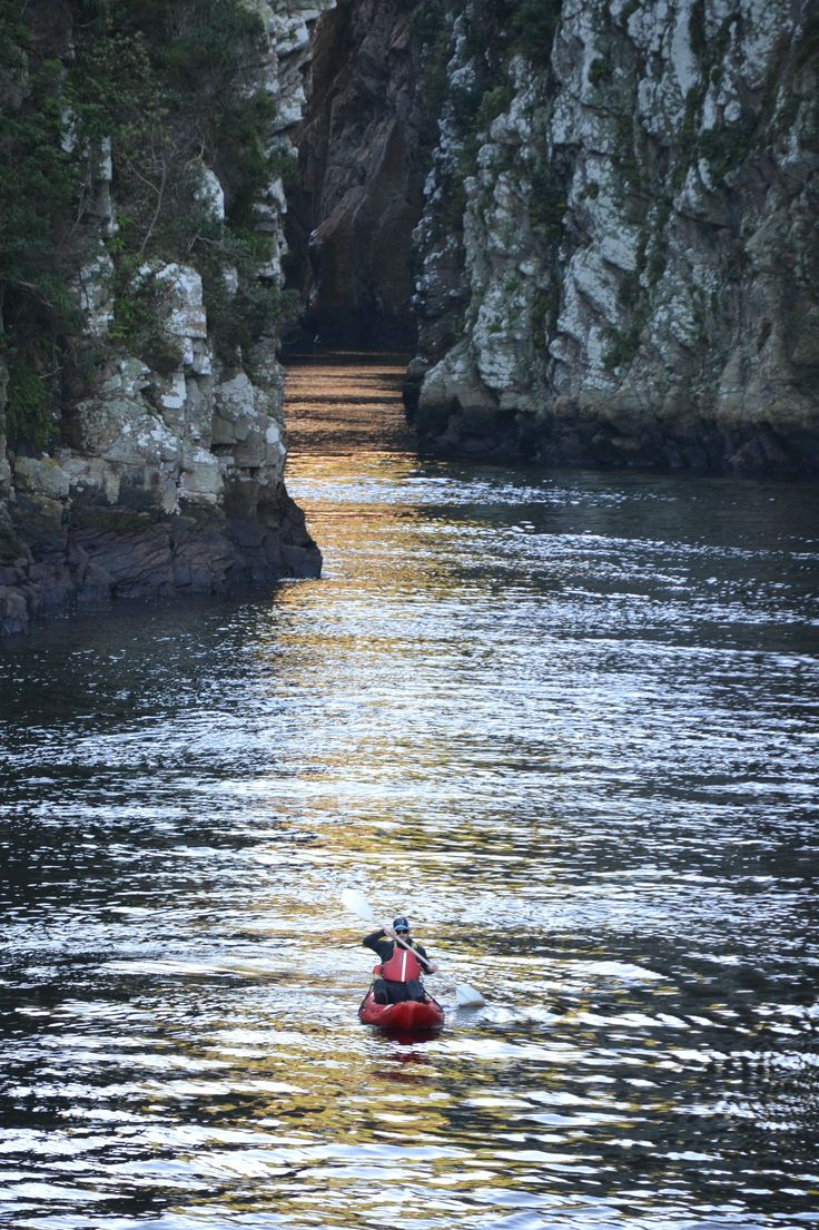 Paddling into the gorge as the afternoon glow shimmers on the water. Stormsrivermouth, South Africa.